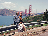 Couple sitting on railing with the Golden Gate Bridge in the background.