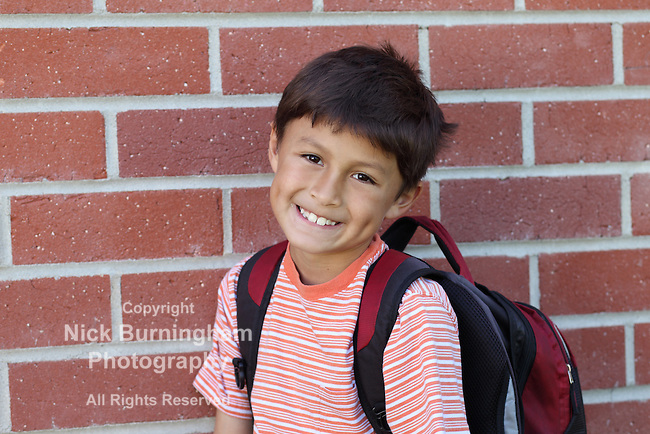 Smiling young schoolboy with backpack gets ready to enter school with copy space to left