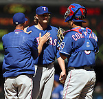 Texas Rangers' starter Ross Detwiler confers with pitching coach, Rick Watts and catcher Carlos Corporan  in their game agains the Seattle Mariners at SAFECO Field in Seattle on April 10, 2015.  The Mariners came from behind to beat the Rangers 11-10.  Jim Bryant Photo. ©2015. All Rights Reserved.