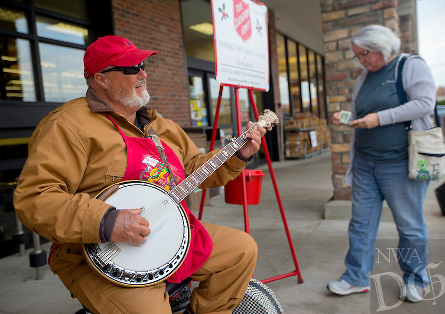 NWA Democrat-Gazette/JASON IVESTER<br /> Gary Shipley of Springdale plays his banjo on Friday, Dec. 2, 2016, outside the Harps in Springdale soliciting donations for The Salvation Army.
