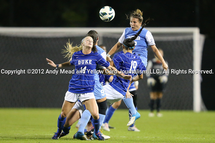 18 October 2012: UNC's Amber Brooks (22) heads the ball over Duke's Erin Koballa (14) and Kim DeCesare (19) and UNC's Maria Lubrano (91). The University of North Carolina Tar Heels defeated the Duke University Blue Devils 2-0 at Koskinen Stadium in Durham, North Carolina in a 2012 NCAA Division I Women's Soccer game.