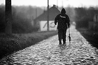 (bit late, but) just before the race passes true, an official measures the exact distance of the cobbled section as the rain makes the pave extremely slippy<br /> <br /> GP Samyn 2016