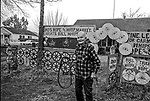"""December 1971:  Modesto, California—Dad Walkling—Dad in front of his well marked house on Thrasher Ave.  I first met Orlando """"Dad"""" Walkling at his house in the airport district of Modesto just before his 104th birthday.  Walkling was born in Indian Territory January 2, 1868, near a town now called McAlester, Oklahoma.  His mother was Shawnee and his father, whom he didn't remember, was an Englishman named Orlando.  He later used the name Walkling instead of his Indian name of Skipocase.  On September 16, 1893, Skipocase O. Walkling, then 25 years old, was among thousands of settlers who rode into the Cherokee Strip Land Run of Oklahoma to make a free land claim.  Walkling told of how he rode into the 226-mile long """"Strip"""" to claim 160 acres.  """"There were thousands of men who waited at the line until noon that day.  The army gun was fired and chaos broke out. Every man carried a gun. There was no law, no sheriff, nothing.  People had to fight for their claim even though they were first.""""  Walkling made a claim, but later gave it up when he had a chance to farm a piece of land in Noble County, Oklahoma.  He cleared the land with six yoke of oxen and planted peach orchards.  He and his first wife ran a combination grocery store and hotel there.  He had nearly 1,000 trees and began a cannery to process the crops.  """"One day when the train came in a woman dressed like a Salvation Army woman handed me a bundle as I stood on the ramp, then she jumped back into the train.  I opened it and there was a pair of twins, a boy and a girl,"""" Walkling said.  He and his wife did not have children, so they adopted the twins legally and raised them.  He said they raised six others but did not adopt them.  He came to Modesto in 1944 at 76 years of age and went to work for a meat firm before he opened a poultry store.  After that store closed, he made bullwhips and wove rope for truckers at his home.  In 1968, Dad Walking, then 100 years old, visited Oklahoma for the 75th annive"""