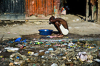 A Haitian woman bathes in a bucket outside the sheet-metal houses in a shanty town close to La Saline market, Port-au-Prince, Haiti, 22 July 2008. Although Latin America (as a whole) is blessed with an abundance of fresh water, having 20% of global water resources in the the Amazon Basin and the highest annual rainfall of any region in the world, an estimated 50-70 million Latin Americans (one-tenth of the continent's population) lack access to safe water and 100 million people have no access to any safe sanitation. Complicated geographical conditions (mainly on the Pacific coast), unregulated industrialization (causing environmental pollution) and massive urban poverty, combined with deep social inequality, have caused a severe water supply shortage in many Latin American regions.