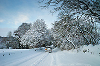 Four wheel drive vehicle in snow-covered lane in Swinbrook, The Cotswolds, UK