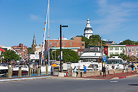 Yachts and sailboats are docked slips in the Annapolis City Dock on Spa Creek, with Main Street and the Capitol dome in view.