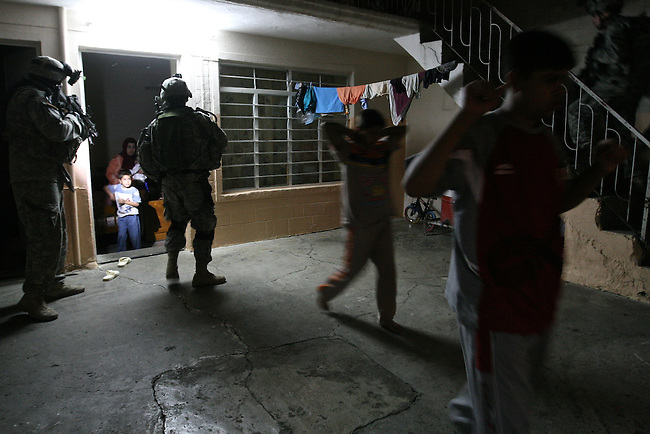 U.S. troops from Company A, 2nd Battalion, 7th Cavalry Regiment order a family out of room so they can search it during a night raid in Mosul, Iraq. The raid targeted an insurgent bomb-making cell that had killed two fellow soldiers the previous day. Nov. 1, 2007. DREW BROWN/STARS AND STRIPES