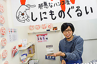 """Yuji Kurosawa holding cat food, """"hanko"""" stamp shop, Yanaka, Tokyo, Japan, April 19, 2012. Yanaka is part of Tokyo's """"shitamachi"""" historic working class wards. Recently it has become popular with Japanese and foreign tourists for its many temples, shops, restaurants and relaxed atmosphere."""