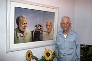 June, 1977. Havana, Cuba. Eighteen years after the Cuban Revolution the first U.S. tourists were permitted to visit Havana. Greggorio Fuentes, the captain of Ernest Hemingway's private yacht, in front of a painting of Hemingway, Hemingways boat, and Fuentes himself. On one of their trips at high sea they met a fisherman trying to tow a giant Marlin fish to the shore, which was the inspiration for Hemingway's famous book, The Old Man and the Sea.