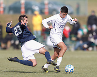 Brandeis defender Matt Brondoli (23) tackles Williams midfielder Malcolm Moutenot (22). NCAA Division III Sectionals. Williams College (white) defeated Brandeis University (blue/white), 2-0, on Hitchcock Field at Amherst College on November 23, 2013.