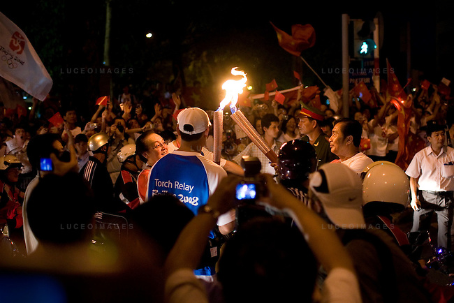 One of 60 torchbearers hands off the Olympic flame completing his leg of the Olympic torch relay on Pasteur Street heading north towards the Tan Son Nhat International Airport in Ho Chi Minh City, Vietnam. Pro-China demonstrators wave flags in support in the background...Thousands of people filled the streets of downtown District 1 in Ho Chi Minh City, Vietnam, to catch a glimpse of one of the 60 torchbearers complete the last leg of the Olympic flame's global journey outside China.  The Olympic torch relay began at the Opera House in the city center and conclude at a stadium near the Tan Son Nhat International Airport, covering a route of 10-13 kilometers. The Olympic flame will head to Hong Kong next. Photo taken Tuesday, April 29, 2008. Kevin German / kevin@kevingerman.com