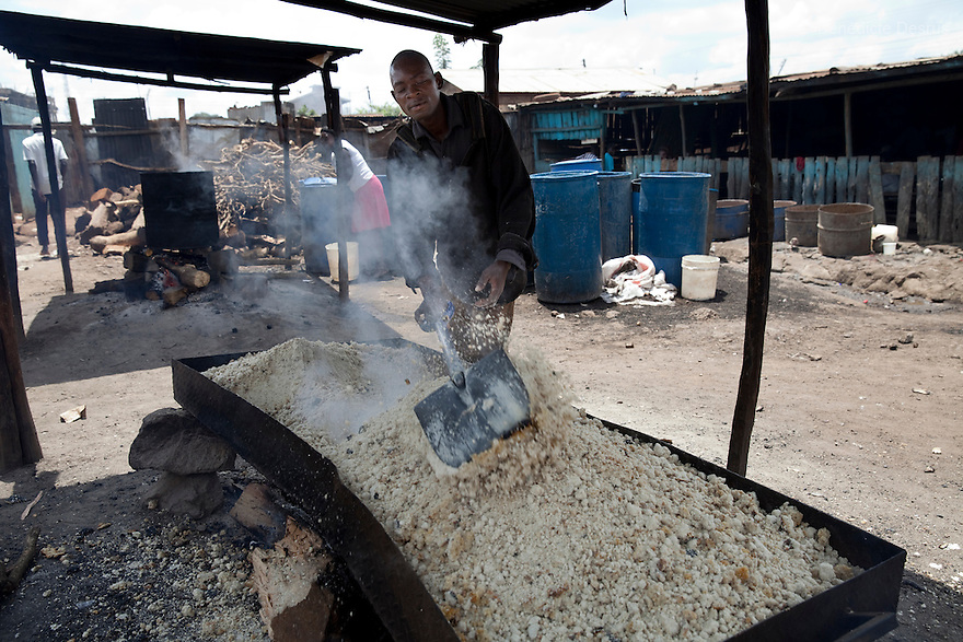 A Kenyan man toasts the preparation to make Busaa, a traditional fermented beer, at the Madiaba Busaa Club in a Nairobi slum on March 27, 2013. Busaa is made by crudely fermenting maize, millet, sorghum or molasses. At Kshs 35 per liter it is much cheaper than a Kshs120 half-liter bottle of commercial beer. The local brew was legalised in 2010 and since then busaa clubs have become increasingly popular. Drinking is on the rise in Kenya, especially among young people. Photo: Benedicte Desrus
