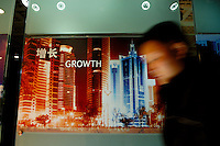 A man passing a panel with a photograph of modern buildings depicting 'growth' at the Shanghai Urban Planning Museum.