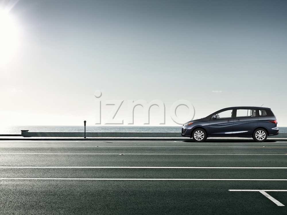 One dark blue 2012 Mazda5 Sport outdoors near the ocean.