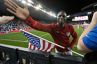 Eddie Johnson hi-fives an American Fan after while holding a USA flag after the United States Men's National Team's won its World Cup Qualifier against Guatemala 3-1 at Livestrong Sporting Park in Kansas City, Kansas on Tue. Oct. 16, 2012.