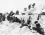 Troops on Utah Beach in Normandy, France on June 9, 1944, take shelter behind a sea wall while awaiting orders to move inland during the invasion by allied troops in June 1944. (AP Photo)