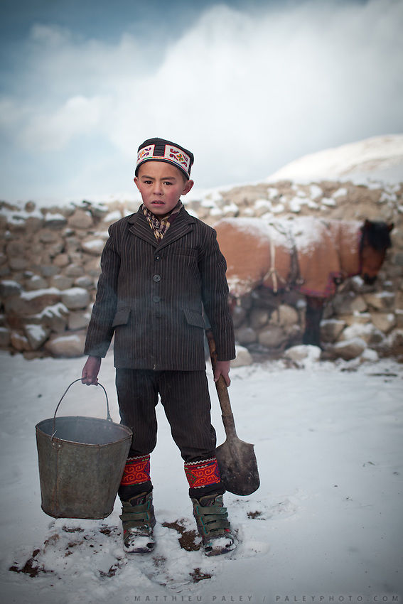 Toorkhan Boi, son of Sufi, taking burning dung from one house to to start the fire in his house..In and around the camp of Ortobil, Manara (Sufi camp), near the borders with China and Tajikistan...Trekking with yak caravan through the Little Pamir where the Afghan Kyrgyz community live all year, on the borders of China, Tajikistan and Pakistan.