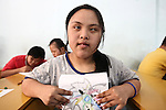 A girl holds a page that she has colored at a center for children affected by dioxin exposure in Da Nang, Vietnam. The Da Nang Association of Victims of Agent Orange/Dioxin says that more than 1,400 children around the city suffer from mental and physical disabilities because of dioxin exposure, a legacy of the U.S. military's use of  Agent Orange and other herbicides during the Vietnam War more than 40 years ago. About 200 children attend three centers operated by the group, which aims to teach the children how to read and write, sew clothes and make handicrafts. Another goal is to provide them with some limited vocational skills, but nearly all who have been sent out to work have eventually returned, unable to integrate into society, says Phan Thanh Tien, association president. The Vietnam Red Cross estimates that 3 million Vietnamese suffer from illnesses related to dioxin exposure, including at least 150,000 people born with severe birth defects since the end of the war. The U.S. government is paying to clean up dioxin-contaminated soil at the Da Nang airport, which served as a major U.S. base during the conflict. But the U.S. government still denies that dioxin is to blame for widespread health problems in Vietnam and has never provided any money specifically to help the country's Agent Orange victims. May 28, 2012.