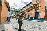 Man walks down the street carrying lumber, El Panecillo, The little bread loaf hill in old town Quito, Ecuador