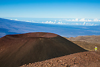 A hiker near the summit of Mauna Kea, with a cinder cone (or pu'u) and the slope of Mauna Loa in the background, Island of Hawai'i.