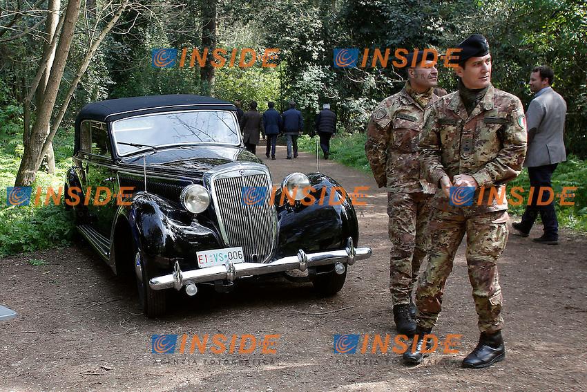 Macchine d'epoca e due militari <br /> Roma 24-03-2016 Da sabato apre, dopo 70 anni di abbandono, il bunker reale, appartenente alla famiglia Savoia. Il bunker fu realizzato presumibilmente intorno al 1940-42, ad una distanza di circa 350m dalla palazzina reale, dentro Villa Ada. L'entrata del bunker, che si trova al livello stradale, permetteva l'entrata delle automobili. La struttura, situata a 200m di profondit&agrave;', ha una struttura circolare. Il bunker aveva un sistema di riciclo e deputazione dell'aria, che permetteva un totale isolamento anche in assenza di energia elettrica. Il sistema di filtraggio veniva azionato tramite energia cinetica, pendolando su una sorta di bicicletta. Completano il rifugio, due bagni, un'anticamera e 2 ambienti di servizio. Il bunker era dotato di una via di fuga secondaria, con l'accesso da una bellissima scala a chiocciola.<br /> Rome 24th March 2016. Opening after 70 years of the Royal bunker, belonged to the Savoy family. The bunker was built between 1940 and 1942 and was 250m far from the Royal House, inside Villa Ada park. The entry of the bunker was made to allow cars entrance. The structure was built 200m deep, inside a hill. The bunker, composed of various rooms, had a complicated system  of aeration, with filters to depurate air, even in lack of electricity. People had to ride on a bicycle to produce kinetic energy. The entrance door, a security and antigas door, has a weight of 5.300 lbs.<br /> Photo Samantha Zucchi Insidefoto