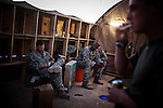 "10/6/2010 FOB Dwyer, Helmand Province, Afghanistan.Soldiers with TF Destiny's FOB Dwyer Medevac team wait for missions outside the recreational tent at their headquarters on the flight line on FOB Dwyer, Helmand Province, Afghanistan...The Helicopter Medevac teams of Task Force Destiny, based at Forward Operating Base Dwyer in Afghanistan's war-torn Helmand Province have a tough job. Servicing a large area that includes still restive southern Marjah, and much of the Helmand River Valley, TF Destiny answers the call to transport gravely wounded US Marines and Afghan civilians from the point of injury in the field to Role 3 trauma centers on bases in the area--often times landing under fire to extract Marines and soldiers that would otherwise succumb to their wounds. After the Medevac helicopter and it's ""chase"" UH-60 Blackhawk companion aircraft get a call, they can be on the ground picking up a patient in as little as 20 minutes--delivering the fallen to a surgical theater within what flight medics refer to as ""the golden hour""--or the hour after a catastrophic injury during which a patients transfer from basic battlefield triage care to a modern trauma surgical unit can mean the difference between life and death. ."