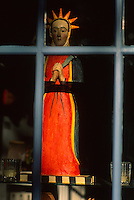 Southwestern religious painted wooden statuette of Mary in a window