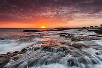 The sun sets in a purple and orange sky over rushing ocean water along the Kona Coast of the Big Island of Hawai'i.