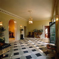 The imposing entrance hall of the Ionic Villa has a geometric tiled floor and walls painted with faux bricks