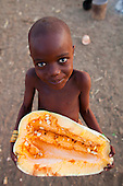 Himba tribe young girl holding a cut squash, Namibia.