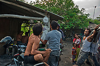 Indonesia - Bangka Island - Rebo - Collectors, miners and pontoon owner weighting the tin collected at the end of the working day. Each pontoon can collect around 15 kg of low concentrate tin per day. Depending on the tin global price, at the end of the day each miner can earn around 15 USD, double the average pay of a farm labourer.This once fishermen village has turned into a miner village since mining is much more profitable than fishing.