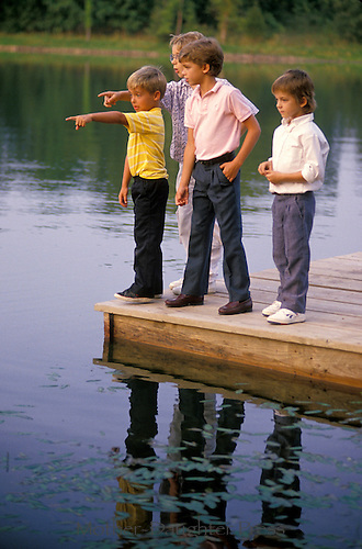 Four young boys standing on dock of lake excitedly pointing at fish