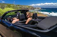 A couple in a black convertible explore the coastline of Maui.