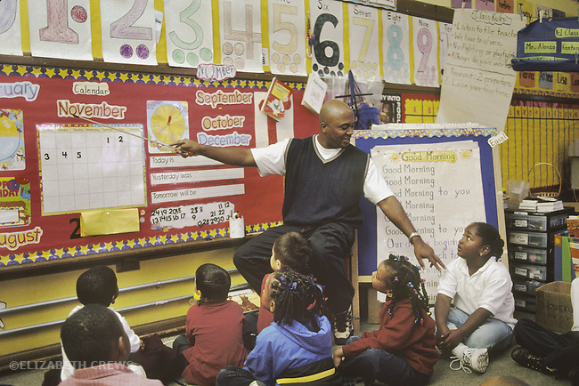 San Francisco, CA African American male kindergarten teacher starting school day by discussing calendar with multiethnic innercity students