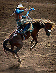 A bareback rider stays on top while in the air during the St. Paul Rodeo.