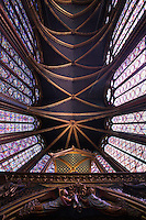 View from below of the choir with the reliquary in the foreground, clerestories and ceiling of the nave, upper chapel of La Sainte-Chapelle (The Holy Chapel), 1248, Paris, France. The upper chapel has four bays and a seven section choir. Each window group has four lancets topped by three rose windows. In the choir, the windows have only two lancets. Fifteen huge mid-13th century windows fill the nave and apse. La Sainte-Chapelle was commissioned by King Louis IX of France to house his collection of Passion Relics, including the Crown of Thorns and is considered among the highest achievements of the Rayonnant period of Gothic architecture. Picture by Manuel Cohen
