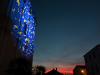 "Italy. Liguria Region. Ospedaletti. Christmas day. An european flag on the catholic church at sunset. The Flag of Europe, or European Flag, is the official symbol representing Europe. Consisting of a circle of 12 golden (yellow) stars on an azure background, it was first adopted in 1955 by the Council of Europe (CoE) to represent the European continent as a whole. Later being adopted the European Union (EU), the flag is sometimes colloquially known as the ""flag of the European Union"", however this term is not official as the flag represents more broadly, the identity and unity of Europe. 25.12.16 © 2016 Didier Ruef"