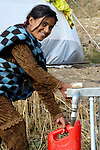 Following an October 8, 2005, earthquake, a young woman gets water from a spigot in a tent city outside Balakot sponsored by Church World Service/Action by Churches Together.
