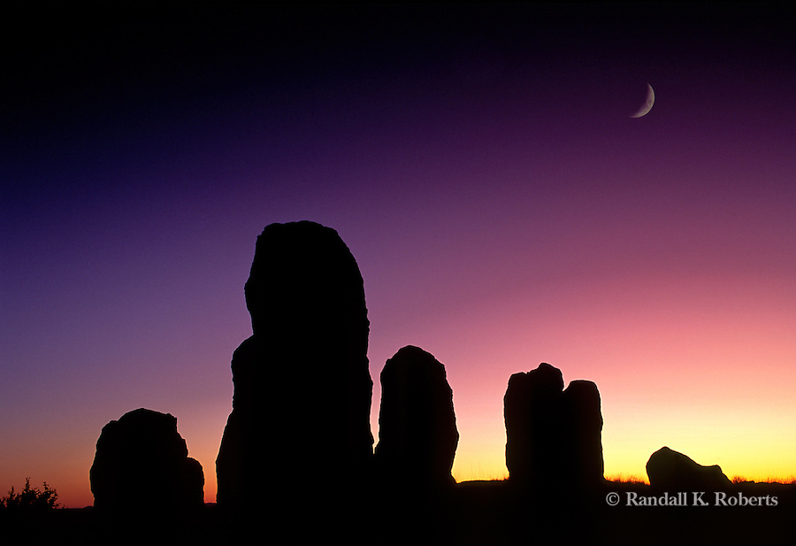 A crescent moon hangs over City of Rocks State Park, New Mexico at sunset.