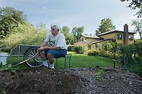John Kaiser, proprietor of the Hamilton Club, tends the garden.