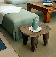 In the living room of a Bridgehampton town house a smooth jade-green ceramic bottle is displayed on a rustic wood footstool also serving as a side table