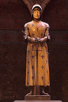Statue of Joan of Arc, 'Jehanne au sacre', 1901, by Prosper díEpinal, in an apsidal chapel in the Cathedrale Notre-Dame de Reims or Reims Cathedral, Reims, Champagne-Ardenne, France. Her armour is bronze, her face ivory, and her tunic is yellow marble with fleurs de lys incrusted with lapis lazuli. The cathedral was built 1211-75 in French Gothic style with work continuing into the 14th century, and was listed as a UNESCO World Heritage Site in 1991. Picture by Manuel Cohen