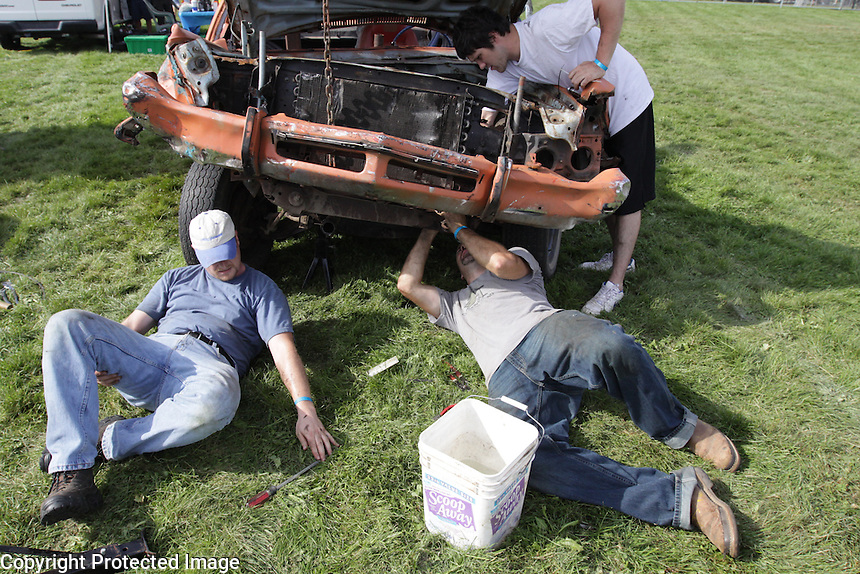 Seth Jennings, left, of Ferndale, Scott Perry of Bellingham, right, and Ty Staeb, standing,  work on The Erickson's car, URAL NW. Demolition Derby at the NW Washington Fair. August 17, 2009 PHOTOS BY MERYL SCHENKER