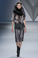 Ella Kandyba walks runway in a black vault print silk chiffon high neck cape top with oversized charcoal raccoon neck gator, and steel vault jacquard skirt with charcoal melton zip-front peplum, from the Vera Wang Fall 2012 Vis-a-gris collection, during Mercedes-Benz Fashion Week Fall 2012 in New York.