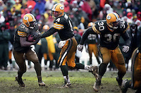 """Brett Favre hands off to Edgar Bennett during the NFC Divisional Playoff Game against the 49ers on January 4, 1997. Dubbed the """"Mud Bowl"""", the Packers emerged the victor 35-14."""
