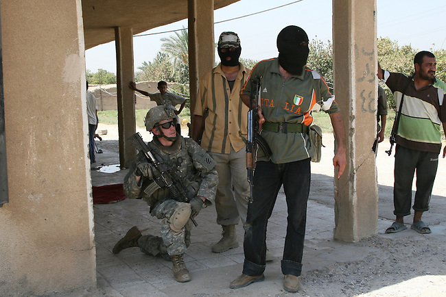 Spc. Michael Collier, 22, of Jacksonville, Fla., of Company D, 3rd Battalion, 15th Infantry Regiment, takes a knee next to a group of Sunni tribal fighters who have switched sides and are helping U.S. soldiers clear al Qaida fighters from the village of Tuwaitha, south of Baghdad. Sept. 5, 2007. DREW BROWN/STARS AND STRIPES