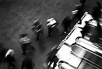Shot from above at Burrard Street Station, looking down upon escalators and people moving in a blurred motion.