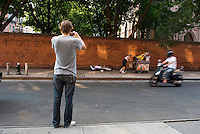 Man aking photograph of a homeless man asleep. Street photography in NY August 3, 2007