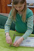 Kinder basteln ein Fensterbild mit Blüten, Mädchen verknotet mit Schnur das Pergamentpapier mit dem Holzrahmen