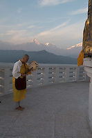 Photo: Alison Wright// Nepal, Pokhara, National Geographic Journeys, Himalayan Highlights, MT7829. The National Geographic group stayed in Pokhara for two nights at the Temple Tree Resort. Japanese Buddhsit nun chanting paryers while circumambulating the Peace Pagoda as the sun sets on Machapuchare, Fish Tail Mountain.
